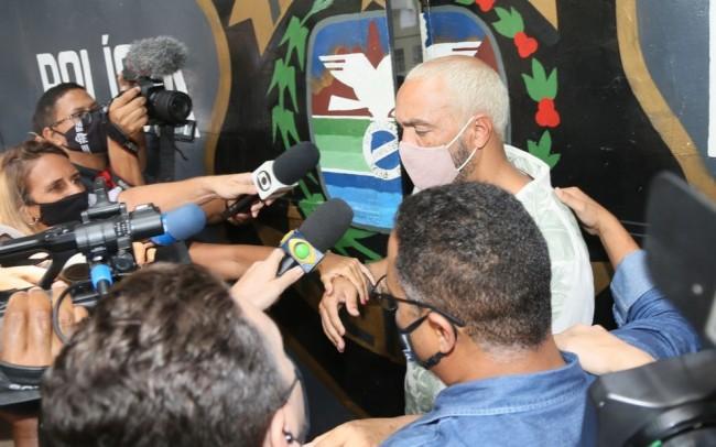 Belo na saída de cadeia na zona norte do Rio de Janeiro; cantor deixou a prisão nesta quinta (18).