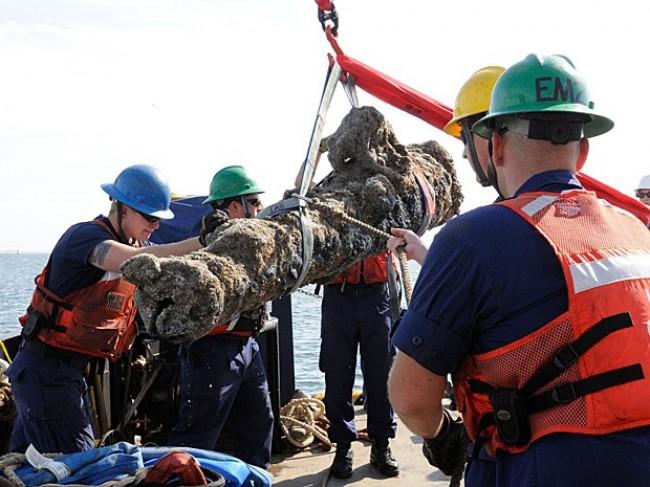 Membros da Guarda Costeira americana erguem um dos canhões recuperados de navio naufragado em 1718 (CRÉDITO: KAREN A. BLUM/NCDCR/AFP)