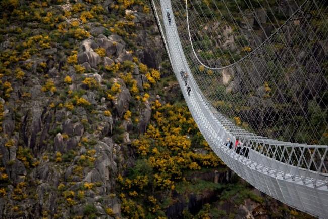 Pessoas corajosas atravessam a maior ponte suspensa para pedestres do mundo (CRÉDITO: VIOLETA SANTOS MOURA/REUTERS)