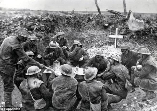 Soldados comendo para celebrar o Natal em uma trincheira parcialmente ocupada pelo túmulo de um companheiro (CRÉDITO: IMPERIAL WAR MUSEUM)